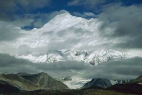 Mount Everest rises up into the upper troposphere. Misty mountain scenes are a common sight since the sudden increase in elevation helps to generate cloud cover.