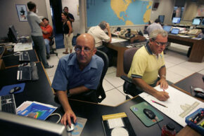 Hurricane specialist Lixion Avila and forecaster Martin Nelson track Hurricane Ernesto at the National Hurricane Center.