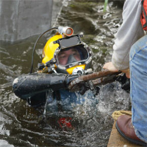 An underwater welder hands off his welding torch after securing the underwater piers that will carry the I-195 roadway in Providence, R.I., in 2005.