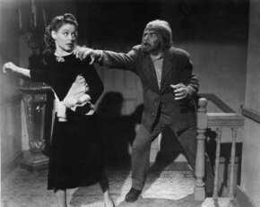 Circa 1945: A werewolf chases a woman up the stairs and grabs her shoulder, from an unidentified film still.