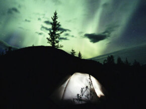 The Northern Lights shine beyond a tent inthe MacKenzie Mountains inCanada