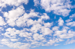 That picture-perfect blue sky punctuated with clouds is compliments of Rayleigh scattering.
