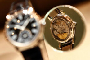 The back of a Patek Philippe wristwatch is reflected in a mirror at the 2009 Baselworld watch and jewelry show in Basel, Switzerland.