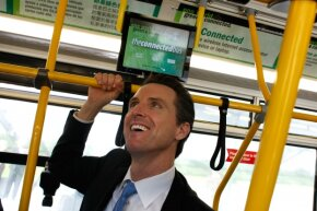San Francisco mayor Gavin Newsom inspects the Connected Bus, which features WiFi, live route information and wait times via touchscreen monitors, and a 'Green Gauge' that gives information about the environmental impact of the bus.
