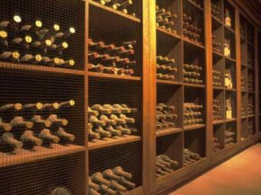Wine cellar in Napa Valley with plenty of aging, dusty bottles. See more wine pictures.