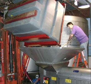 Grapes get loaded into a crusher at the winery.