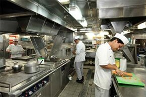 Filipino cooks preparing meat in the commercial kitchen of a cruise ship. Most cruise ship crew members are from developing countries.