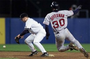 Yankees second baseman Chuck Knoblauch (L) drops the ball as he takes the throw in the top of the 10th inning from Derek Jeter; yet, the umpire ruled that Red Sox second baseman Jose Offerman was out.