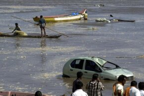 People gaze out at the floodwaters in Madras, India, after the December 2004 tsunami.