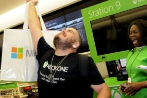 The first consumer to buy an Xbox One at the midnight release event at the Florida Mall in Orlando, Fla. raises his purchase triumphantly in the air.