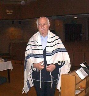 This gentleman wears a white yarmulke and a prayer shawl (a tallit).