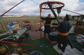 A Mongolian family assembles their yurt.