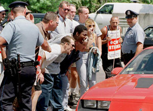 Teamsters yell at scabs as they drive across the picket line during a strike.