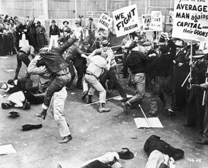 Strikers fight with a group of scabs as they try to cross a factory picket line in this photo from 1935. See more corporation pictures.
