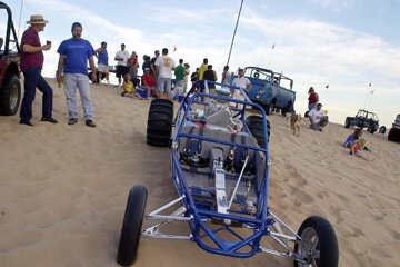Steve Nickell, far left, and Terry Howe look over a dune buggy during a sunset cook-out on Nov. 22, 2002, at Imperial Sand Dunes Recreation Area near Glamis, Calif.