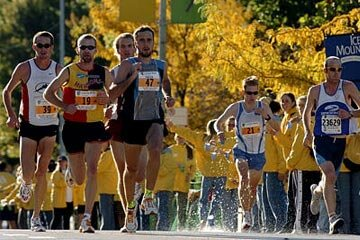 Runners grab water at an aid station during the 2004 Chicago Marathon as other participants run past.