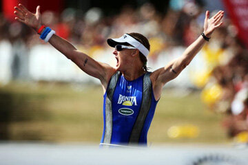 Jo Lawn raises her arms in triumph after winning the 2010 Ironman New Zealand triathlon in March 2010.