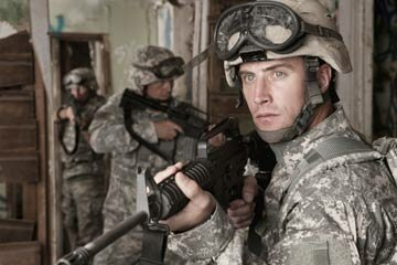 A group of U.S. Army soldiers clear an abandoned building using machine guns. Fully automatic machine guns are seen mainly in the military.