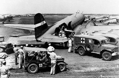 """Troops, arms, food, and, as here, the wounded -- Douglas C-47s carried them all. """"Aeromedical evacuations"""" such as this were, for injured soldiers, the first leg of long journeys to safety and, sometimes, home."""