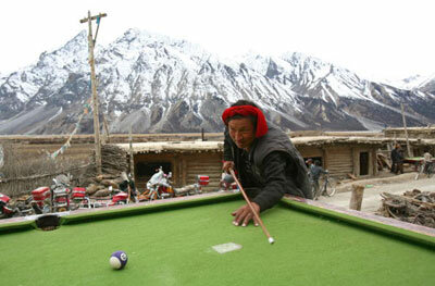A Tibetan villager plays pool in the outskirts of Basu County of Tibet Autonomous Region, China. The Tibetans are accustomed to the high altitude of their region, though many visitors are afflicted with high altitude sickness.