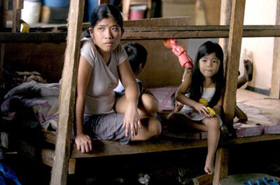 Rachel Santiago with her two children in their shack, built in a squatting village in Manila, Philippines