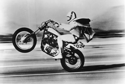 American stunt performer Evel Knieval pulls a 'wheelie' with his motorcycle.
