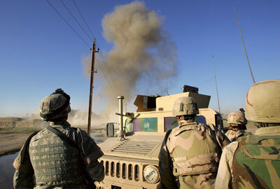 U.S. Army bomb team members watch the controlled detonation of an improvised explosive device (IED) to clear it from the streets in Baghdad, Iraq.