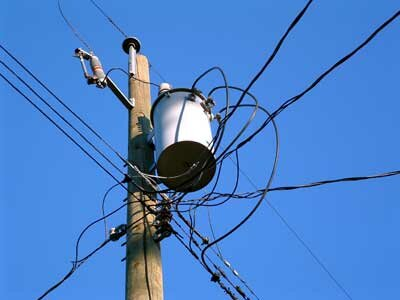 Power-distribution systems connect into the ground many times. Note the wire trailing down the side of the utility pole in this photo.