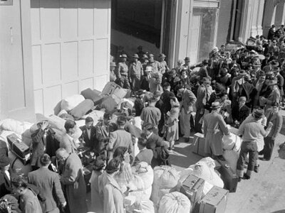As military police stand guard, people of Japanese descent wait at a transport center in San Francisco on April 6, 1942, for relocation to an internment center at Santa Anita racetrack near Los Angeles.