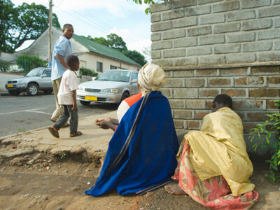 A blind woman and her daughter ask for money from passersby in Blantyre, Malawi. One of the Rotary Club's seven priorities is providing service to people in need.