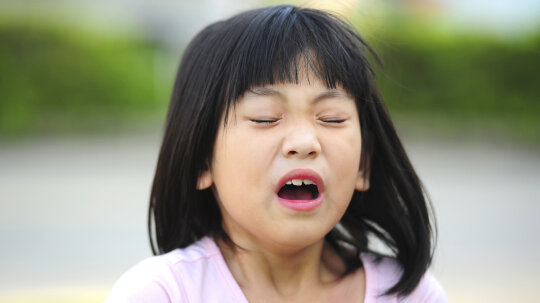 Why does tickling the roof of your mouth with your tongue stifle a sneeze?