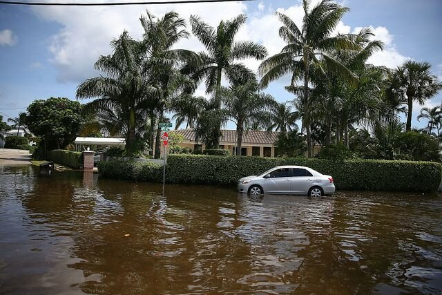 A vehicle drives through flooded streets caused by the combination of the lunar orbit which caused seasonal high tides and what many believe is the rising sea levels due to climate change on September 30, 2015, in Fort Lauderdale, Florida.
