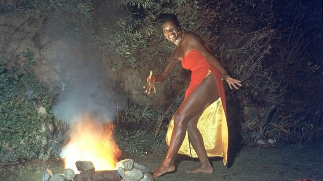 "Maya Angelou wears a red dress while dancing next to a fire in a promotional portrait taken for the cover of her album ""Miss Calypso."""