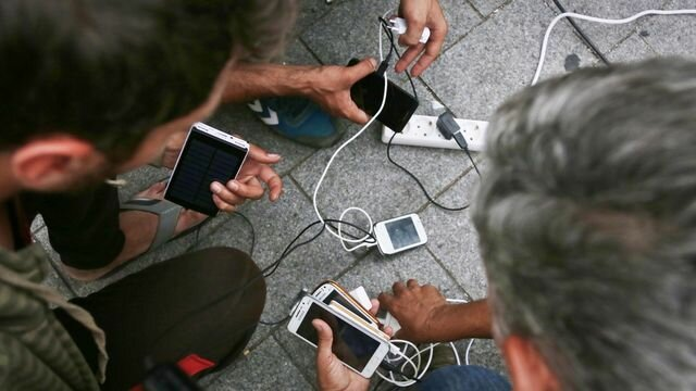 Migrants recharge their phones