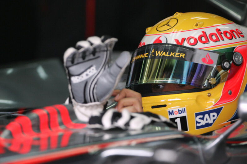 British McLaren-Mercedes driver Lewis Hamilton puts his gloves on in the pits of the Sakhir racetrack, in Manama, during the second practice session of the Bahrain Formula One grand Prix. (KARIM SAHIB/AFP/Getty Images)