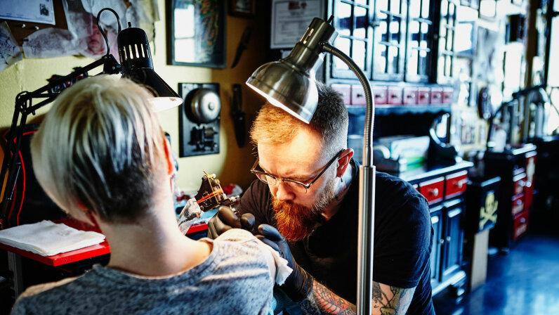 man tattooing woman