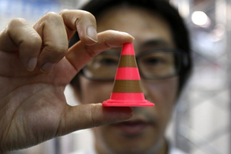 A staff member of Nihon Binary shows an Acrylonitrile butadiene styrene pylon (similar to a plastic traffic cone) which was printed by the 3-D printer MakerBot Replicator 2X during the International Robot Exhibition 2013 in Tokyo. © YUYA SHINO/Reuters/Corbis