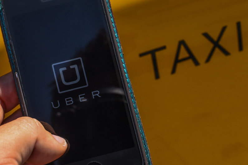 The smartphone app 'Uber' logo is displayed on a mobile phone next to a taxi in Barcelona, Spain. (David Ramos/Getty Images)