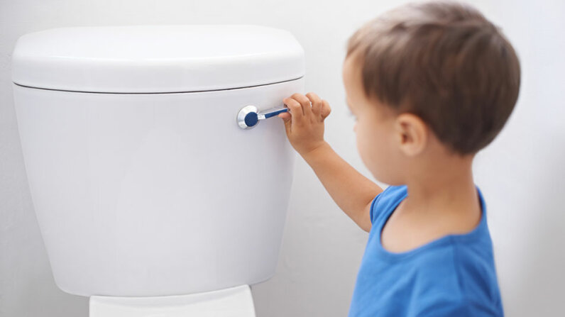 boy flushing toilet