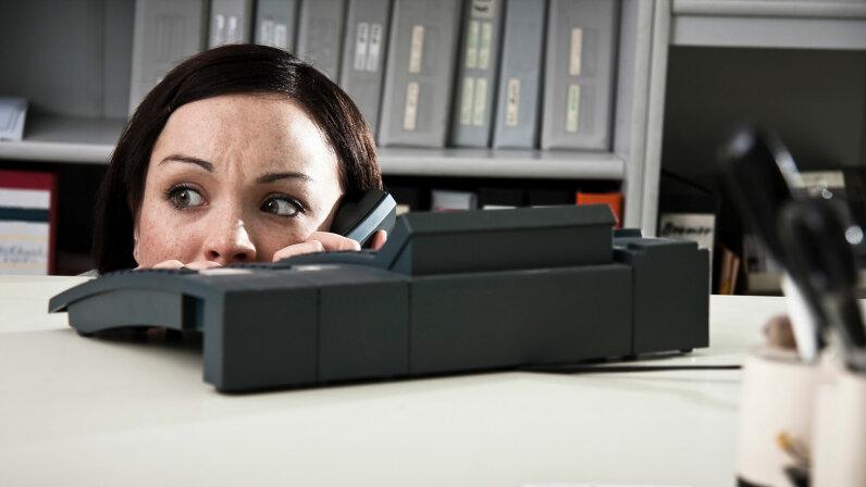 woman hiding by desk