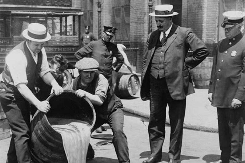 The New York City deputy police commissioner (right) watches agents pour liquor into a sewer following a raid during the height of Prohibition. The U.S. government also poisoned liquor to discourage illicit drinking. Buyenlarge/Getty Images