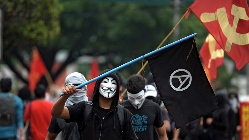A man wearing a Guy Fawkes mask flies an anarchy flag as he takes part in a May Day demonstration for workers' rights in El Salvador in 2012. Many anarchists have adopted the Guy Fawkes mask, made famous in the graphic novel 'V is for Vendetta.' Jose CABEZAS/AFP/Getty Images