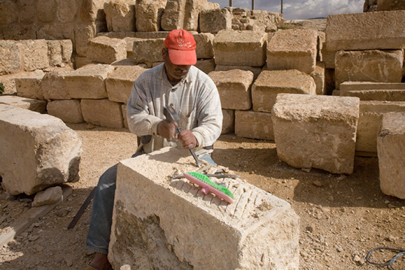 A modern stonemason continues preservation efforts on the 2,000-year-old Roman city of Jerash, Jordan, using some techniques that a stonemason from that time period might have recognized.  © Dave Bartruff/Corbis