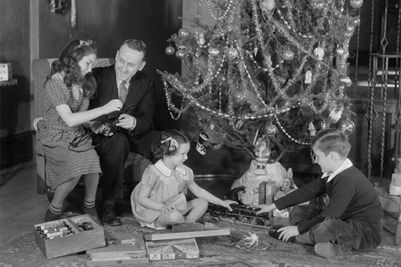 A father and his three children enjoy a model train at Christmas in the 1930s. © H. ARMSTRONG ROBERTS/ClassicStock/Corbis