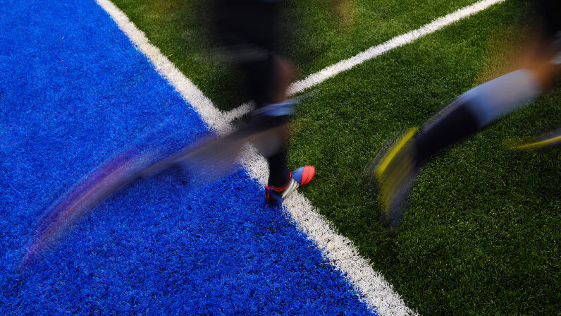 artificial turf field with rugby players on it