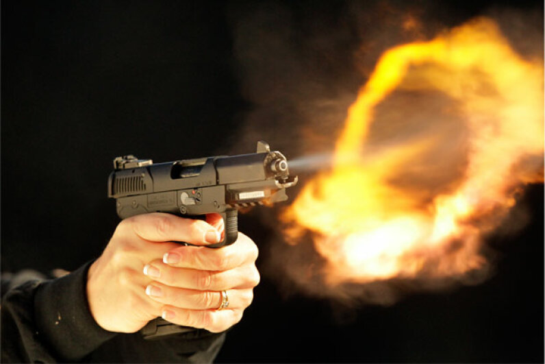 Almost unseen by the naked eye, a flash fire appears after firing the FN Five-seveN single-action semi-automatic pistol. © Tom Fox/Dallas Morning News/Corbis
