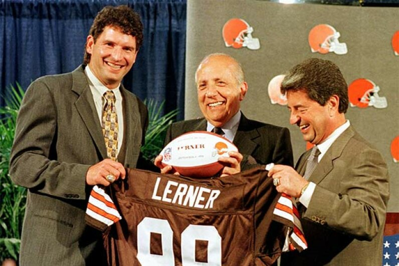 Owner of the Cleveland Browns Alfred Lerner (C) and former Cleveland Browns quarterback Bernie Kosar (L) hold up a team jersey and football at a press conference to announce that the team was again part of the National Football League in 1998. ANTHONY ONCHAK/AFP/Getty Images