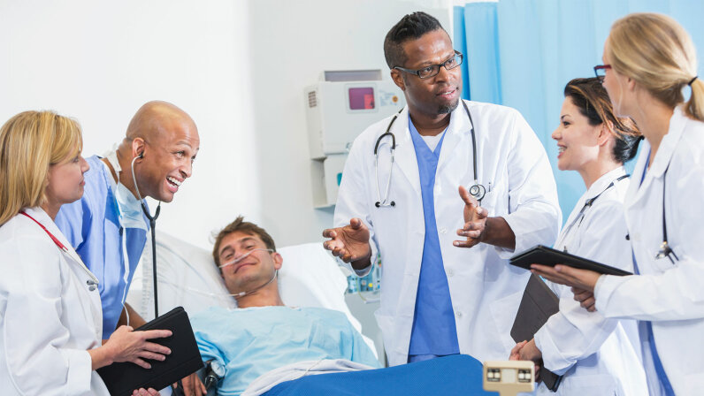 Group of medical students on rounds with doctor and patient