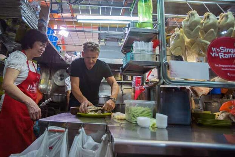 British chef Gordon Ramsay visits owner Foo Kui Lian of the Tian Tian chicken rice stall at the Maxwell Food Centre in Singapore to learn about the dish in 2013. Nicky Loh/Getty Images