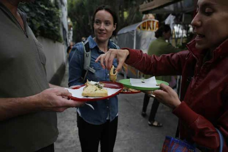 Eat Mexico guide Natalia Gris (R) splits quesadillas with tourists in Mexico City in 2013. Founded in 2010, Eat Mexico is the only culinary tour operator in the country that focuses exclusively on street food and markets. © TOMAS BRAVO/Reuters/Corbis